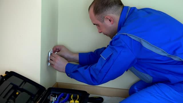 vídeos de stock, filmes e b-roll de homem profissional do eletricista que trabalha com chave de fenda na tomada. - eletricista