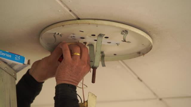 vídeos y material grabado en eventos de stock de bombilla de torsión eléctrica profesional que instala la luz - descarga eléctrica