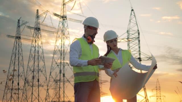 professional electricians discussing electrical project near power line. - zagadnienia filmów i materiałów b-roll