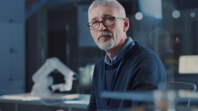 professionell elektronik design ingenjör bär glasögon fungerar på laptop i forsknings laboratoriet, svängar och leenden på kameran. i bakgrunden tung industri robotic och computern komponenterna - titta mot kameran bildbanksvideor och videomaterial från bakom kulisserna