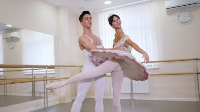 Professional, emotional ballet dancers practicing in the gym or hall with minimalism interior. Couple dancing a sensual dance before performance. Slow motion