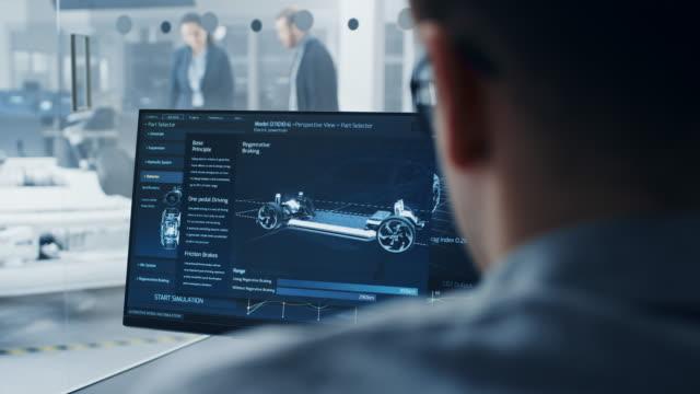 профессиональный инженер работает на компьютере с 3d-программным обеспечением cad и тестирует прототип шасси электромобиля с колесами, бата� - моторное транспортное средство стоковые видео и кадры b-roll