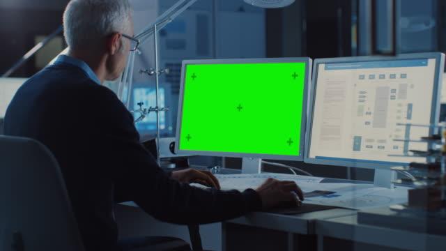 Professioneller Ingenieur arbeitet auf Computer mit Green Mock-up Screen und Electronics Motherboard Blueprint Showing Display. In der Agentur für Industriekompetentechnik im Hintergrund. Über den Shoulder-Schuss – Video