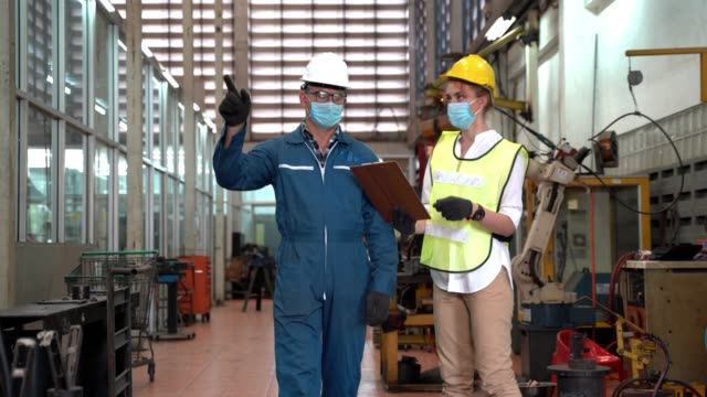 Professional engineering workers walk and check in warehouse factory. Manager discuss inspection report paper for internal audit. Quality assurance for manufacturing. Concept Engineer Operating.