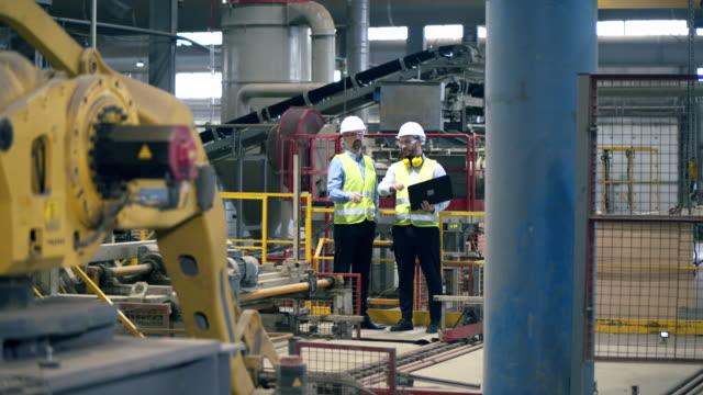 専門技術者がレンガ工場で機器をチェックします。 - 制服点の映像素材/bロール