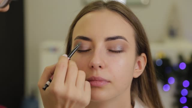 vídeos de stock e filmes b-roll de professional eye makeup. stylist makeup artist applies makeup to a young woman with a special brush in a beauty salon - rímel