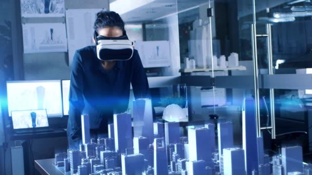 vídeos y material grabado en eventos de stock de profesional arquitecto femenino usando gestos hace con casco de realidad aumentada, muestra las estadísticas para el modelo 3d de la ciudad. alta tecnología oficina uso realidad virtual aplicación de software de modelado. - arquitecto