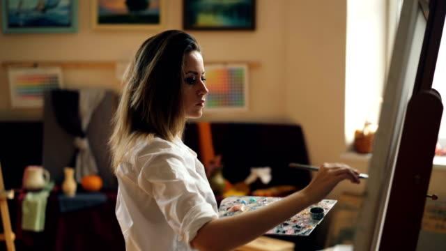 professionelle künstlerin arbeitet im atelier malerei meereslandschaft mit ölfarben und pinsel. schönes mädchen konzentriert sich auf ihre kreative arbeit. - künstlerischer beruf stock-videos und b-roll-filmmaterial