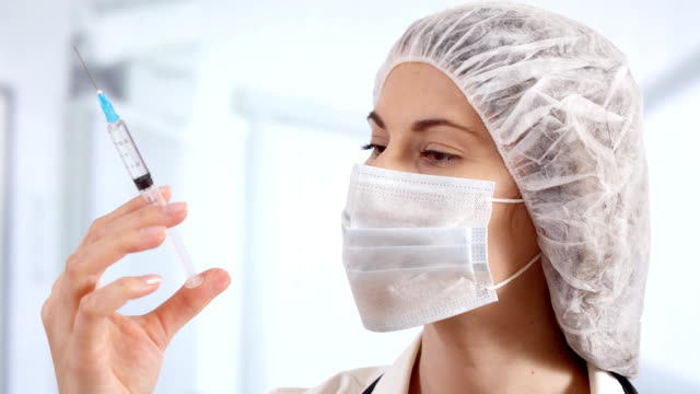 professional female doctor in hospital room holding disposable syringe. woman physician at work - science research stock videos & royalty-free footage