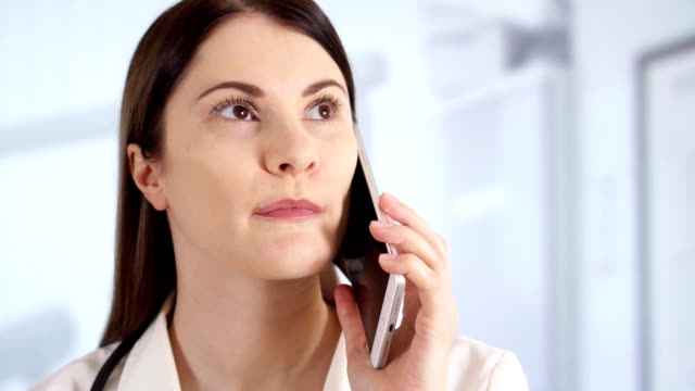 Professional female doctor in hospital room talking on phone with patient. Woman physician at work video