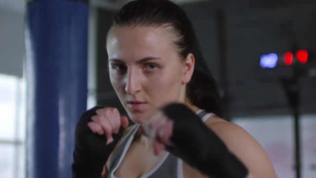 Professional Female Fighter Punching at Camera and Posing in Gym