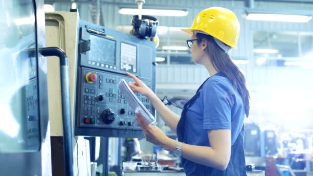 professionell kvinnlig operatör i hård hatt inställningen upp / programmering cnc-maskin med kontrollpanelen i en stor fabrik. - cnc maskin bildbanksvideor och videomaterial från bakom kulisserna