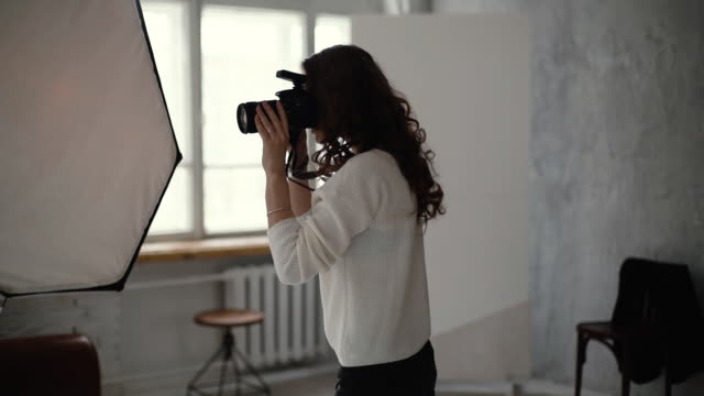 Professional female photographer in casual clothes takes photos in photo studio.