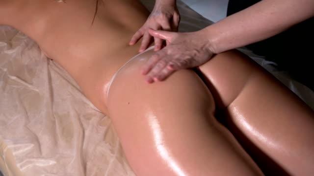 professionell kvinnlig sjukgymnast utför en massage på en patienter skinkorna - bum bildbanksvideor och videomaterial från bakom kulisserna