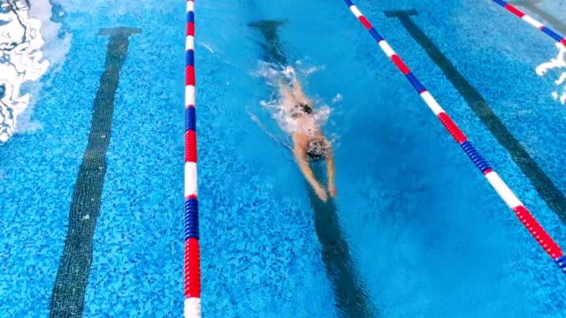 vídeos de stock e filmes b-roll de professional female swimmer in a swimming pool. aerial view. 4k. - campeão desportivo
