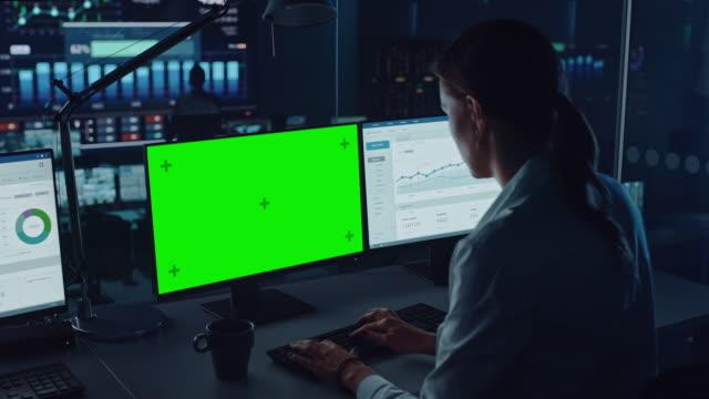 professionella finansiella dataanalytiker som arbetar på en dator med grön skärm i modern övervakningskontor med live analytics-flöde på en stor digital skärm. övervakningsrum med finansspecialister. - server room bildbanksvideor och videomaterial från bakom kulisserna