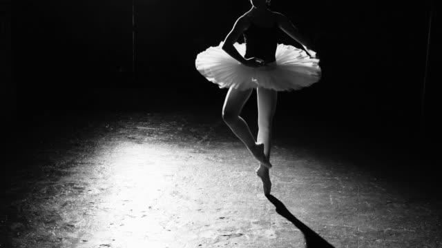 professionell flexibla ballerina dans på hennes pointe balettskor i rampljuset på svart bakgrund i studio. kvinna visar klassisk balett pas tutu och pointe skor. svart och vitt sköt. - piruett bildbanksvideor och videomaterial från bakom kulisserna