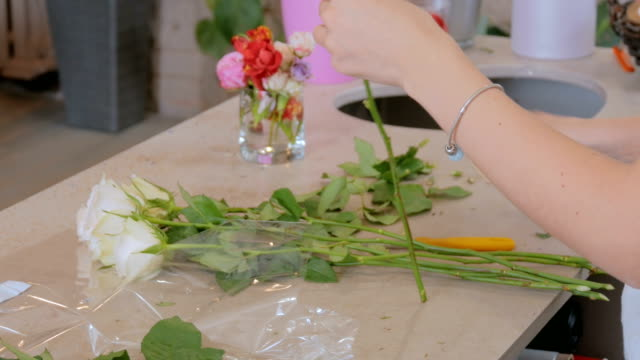 professional floral artist working with flowers at studio - video di bancarella video stock e b–roll