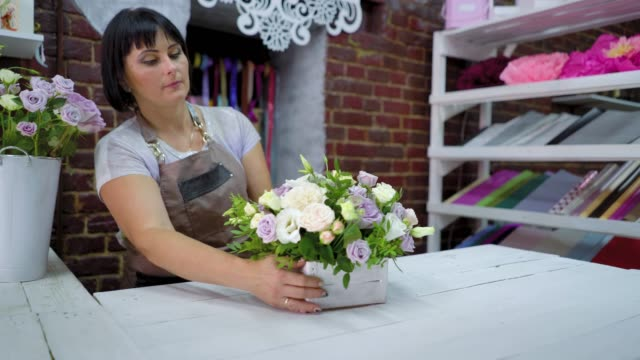 professional florist arranging beatiful flower composition in wooden box in floral design studio