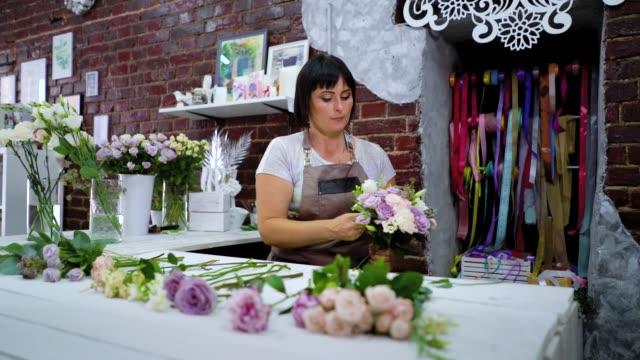 professional florist arranging flower wedding bouquet in floral design studio