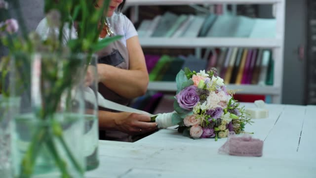 professional florist arranging with ribbon flower wedding bouquet in floral design studio