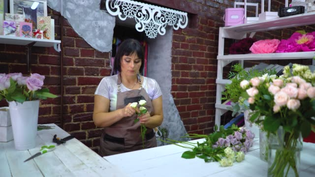 Professional florist clearing and inspecting white rose branch from dry petals