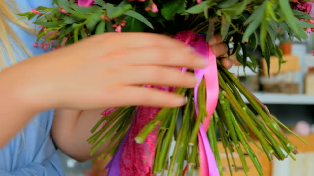 Professional florist holding and checking bouquet at studio video