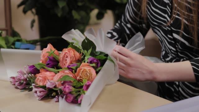 il fioraio professionista sta preparando un bouquet. bellissimo bouquet per la giornata internazionale della donna - bouquet video stock e b–roll