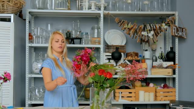 vidéos et rushes de fleuriste professionnel faire beau bouquet au magasin de fleurs - composition florale