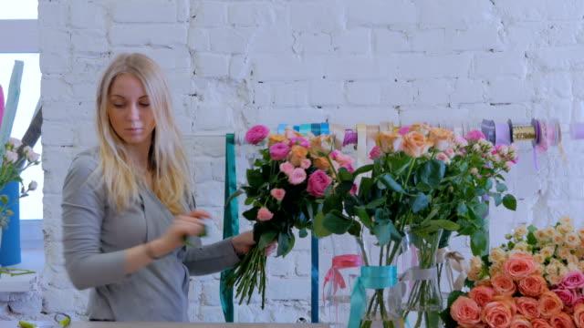 vídeos de stock e filmes b-roll de professional florist making beautiful bouquet at flower store - molho arranjo