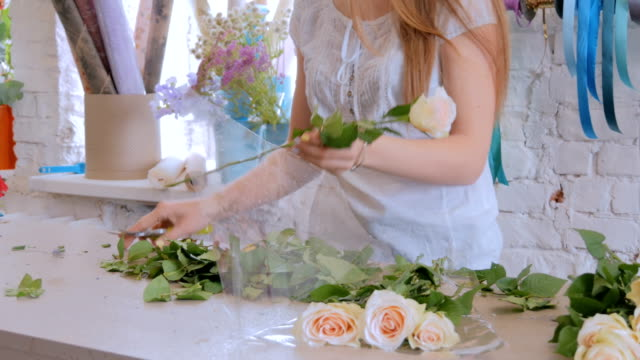 Professional florist working with flowers at studio video