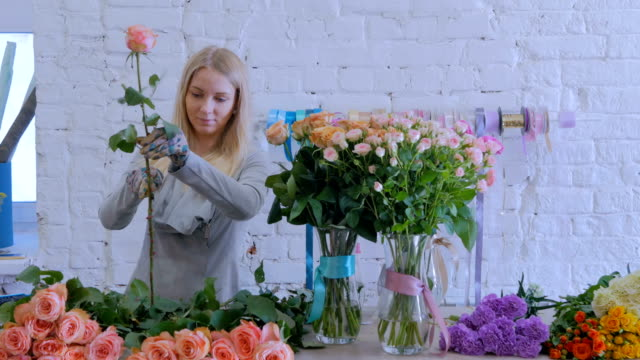 professional florist working with flowers at studio - stelo video stock e b–roll