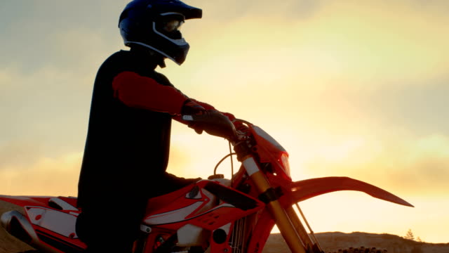 professional fmx motorcycle rider prepares to start driving on his bike over hard sandy off-road terrain. sun is setting. - freestyle motocross video stock e b–roll