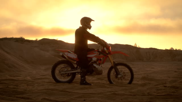 Professional FMX Motorcycle Rider Rests on His Bike and Overlooks Hard Sandy Off-Road Terrain. Sun is Setting. video
