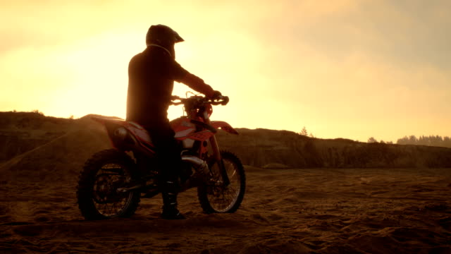 professional fmx motorcycle rider rests on his bike and overlooks hard sandy off-road terrain. sun is setting. - motocross video stock e b–roll