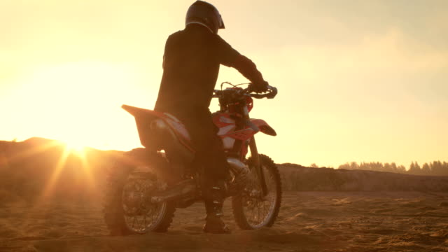 Professional FMX Motorcycle Rider Twists Full Throttle Handle and Starts Riding on the Sandy Off-Road Track. Scenic Sunset. video