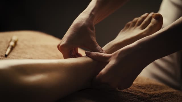 Professional foot massage. Professional foot massage. Authentic footage of luxury spa treatment. Charming light. Shallow depth of field. Stylized and colored. massage oil stock videos & royalty-free footage