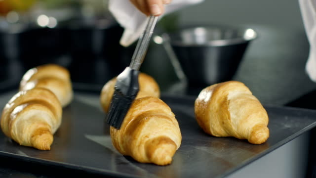 professional french baker butters croissants. - french food stock videos and b-roll footage