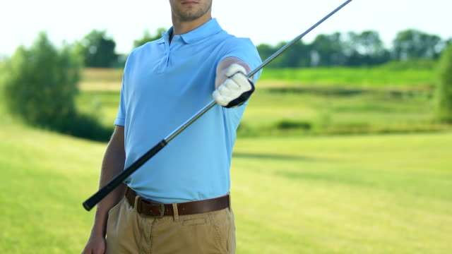 Professional golf player warming up muscles swinging club in hand before game