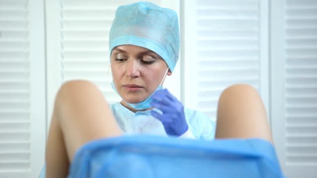muayene sırasında kadın serviks örneği alan profesyonel jinekolog - rahim boynu stok videoları ve detay görüntü çekimi