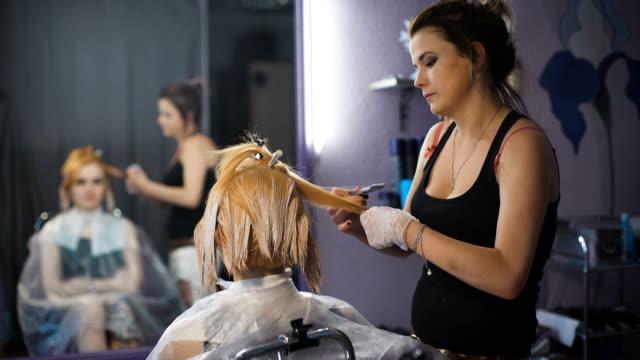 la colorazione dei capelli professionale salone di bellezza. la ragazza nella poltrona cliente che guarda allo specchio riflesso in - guanto indumento sportivo protettivo video stock e b–roll