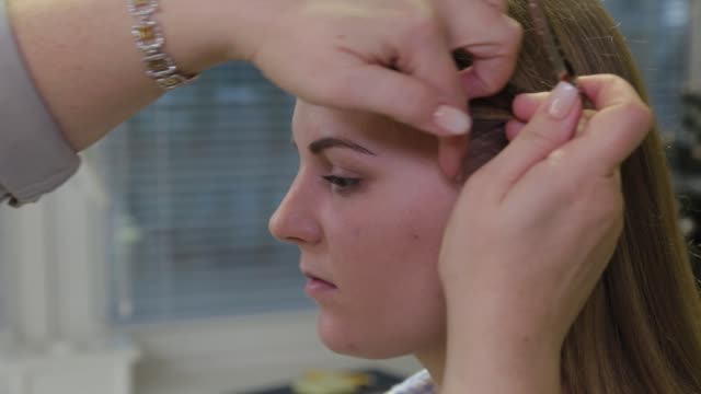 Professional hairdresser puts a hairpin on the head of a girl