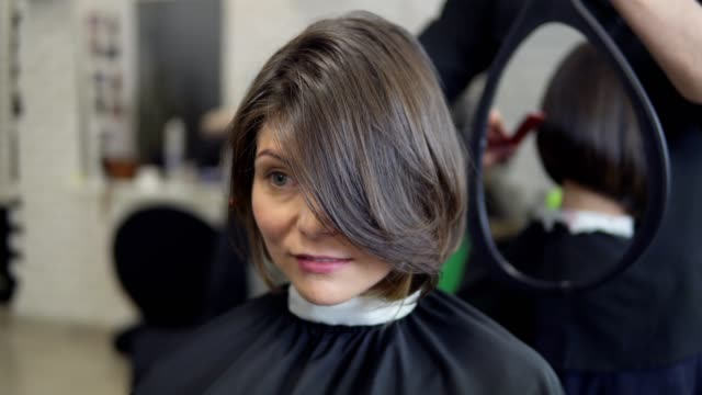 Professional Hairdresser Shows Short Haircut With Mirror To Handsome Satisfied Female Client In Professional Hairdressing Salon Stock Video Download Video Clip Now Istock