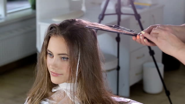 Professional hairdresser, stylist coloring teen girl hair video