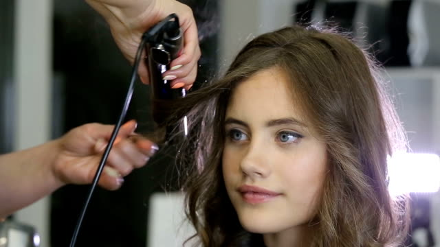 Professional hairdresser stylist curling up teen girl hair video