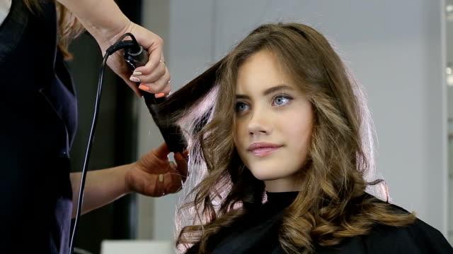 十代の少女の髪をカーリング プロの美容師スタイリスト - 美容院点の映像素材/bロール