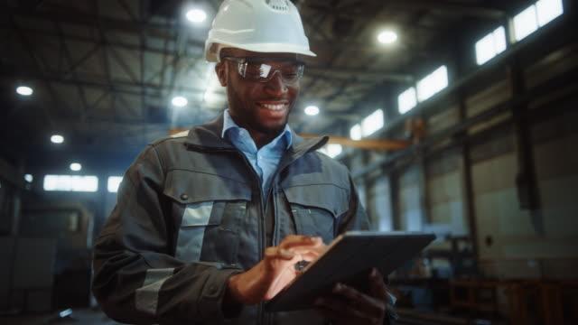 profesyonel ağır sanayi mühendisi / i̇şçi giyen güvenlik üniforma ve hard hat tablet bilgisayar kullanır. gülen afro-amerikan sanayi uzmanı bir metal i̇nşaat üretiminde yürüyüş. - i̇malat ekipmanları stok videoları ve detay görüntü çekimi