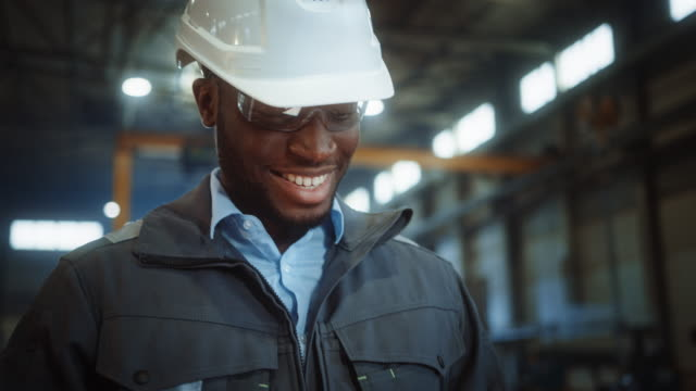 Professional Heavy Industry Engineer/Worker Wearing Safety Uniform and Hard Hat Uses Tablet Computer. Smiling African American Industrial Specialist Walking in a Metal Construction Manufacture. Professional Heavy Industry Engineer/Worker Wearing Safety Uniform and Hard Hat Uses Tablet Computer. Smiling African American Industrial Specialist Walking in a Metal Construction Manufacture. manufacturing equipment stock videos & royalty-free footage
