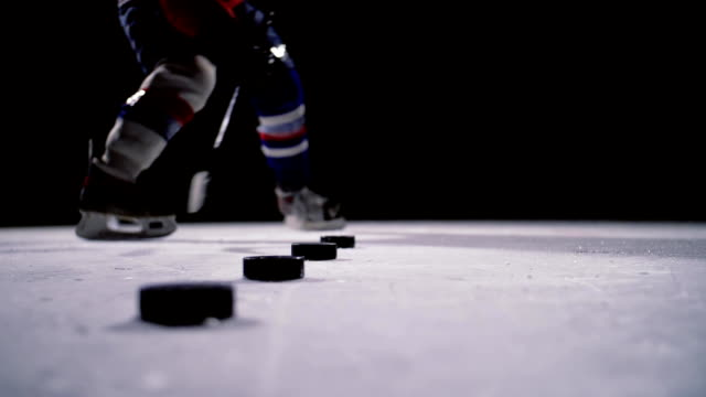 professional hockey player produces a shot on goal at ice arena. close-up. slow motion - praticare video stock e b–roll
