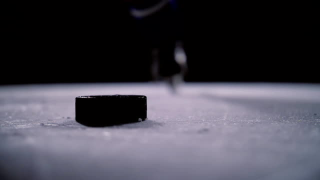 professional hockey player produces a shot on goal at ice arena. close-up. slow motion - hockey stock videos and b-roll footage